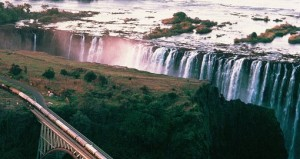 Aerial view of Victoria Falls with train on the bridge in the foreground